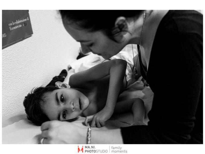 Progetto di fotografia documentaria: I Rari. La mamma consola la figlia durante una visita medica in ospedale a Reggio Emilia.