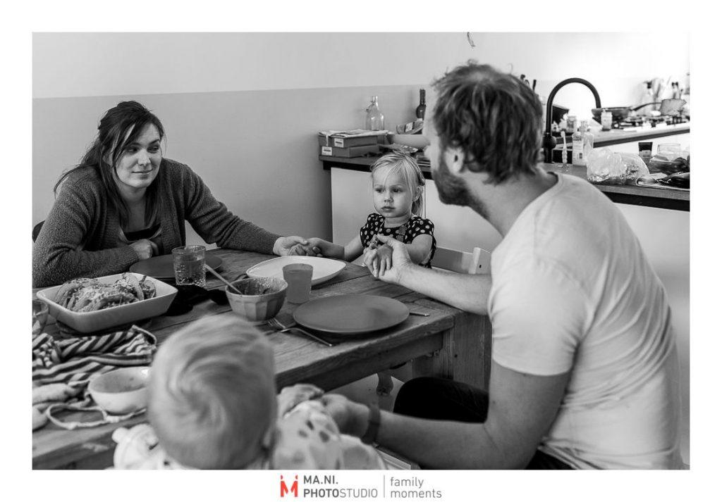 genitori e figli dicono la preghiera prima della cena