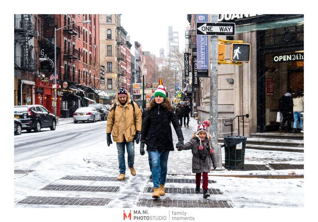 Una famiglia passeggia  per le strade di New York City dopo una tempesta di neve